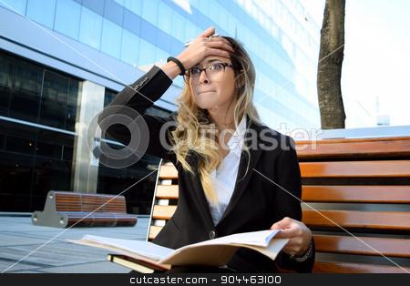 Worried business woman outside her office stock photo, Worried  business woman sitting on a bench outside her office. Professional woman on her coffee break. by nicolas menijes