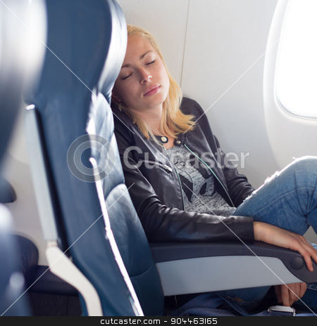 Lady traveling napping on a plain. stock photo, Tired blonde casual caucasian lady napping on uncomfortable seat while traveling by airplane. Commercial transportation by planes. by kasto