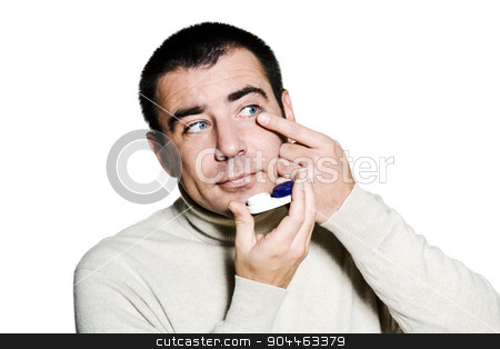 man inserting a contact lens in his eye stock photo, portrait of one  man inserting a contact lens in his eye in studio isolated on white isolated background by Ishadow