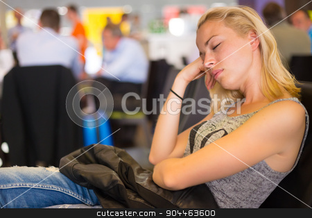 Tired female traveler waiting for departure. stock photo, Tired female traveler waiting for departure, sleeping on the gates bench with jacket by her side.  Tireing traveling. by kasto