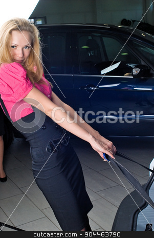 Attrractive woman take suitcase from car stock photo, Travelling young woman take suitcase from car by Aikon
