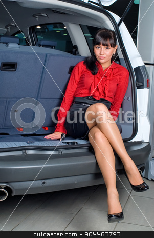Attractive woman in luggage compartment stock photo, Beautiful girl sitting in luggage compartment of car by Aikon
