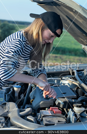 Young Blond Woman With Her Broken Car stock photo, young blond woman with her broken car. The girl is angry by Aikon