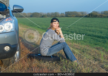 Young Blond Woman With Her Broken Car stock photo, Young attractive blond sad woman with her broken car by Aikon