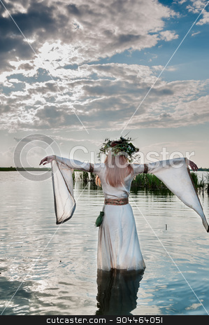 Beautiful woman with flower wreath in watet stock photo, Attractive Woman with Wreath of Flowers walking in water of lake. Back view (Russian traditional holiday celebration) by Aikon