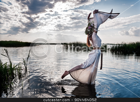 Beautiful woman with flower wreath relaxes stock photo, Attractive young woman with wreath of flowers walking in lake water. Russian traditional Ivan Kupala holiday celebration by Aikon