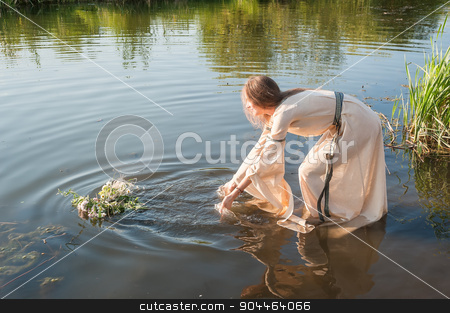 Beautiful girl relaxes in water stock photo, Attractive woman in traditional dress in water of lake. Russian traditional Ivan Kupala holiday celebration by Aikon