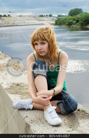Pretty girl on river bank stock photo, Young beautiful woman sitting on river bank by Aikon