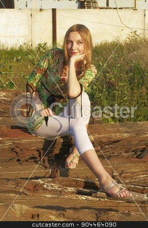Pretty woman on industrial background stock photo, Young attractive woman sitting on old railway cross tie by Aikon