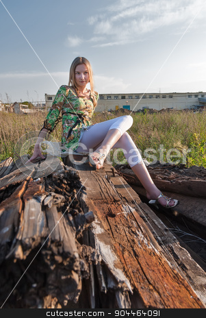 Pretty girl on industrial background stock photo, Young attractive woman sitting on old railway cross tie by Aikon