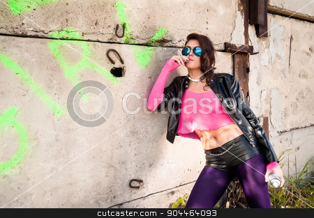 Pretty girl in leather jacket smokes stock photo, Young beautiful woman in sunglasses with spray paint smokes at wall background by Aikon