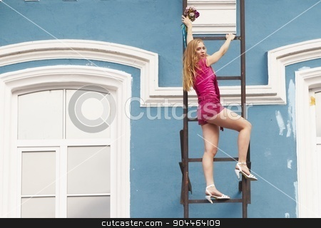 Young attractive woman on stair stock photo, Young beautiful woman climbing on fire stairway of old building by Aikon