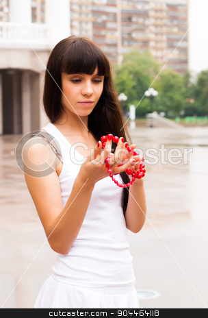 Pretty girl with red beads stock photo, Beautiful girl with red beads at city background by Aikon