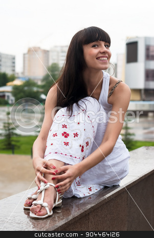 Attractive smiling woman sits over city background stock photo, Young beautiful smiling woman sits over city background by Aikon