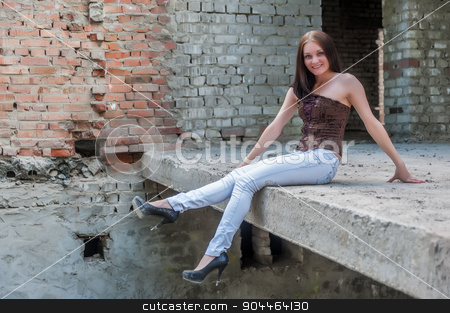 Grunge portrait of a woman in urban ruins stock photo, Beautiful brunette girl against background of ruins by Aikon