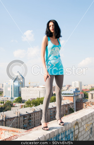 beautiful woman standing on roof stock photo, Beautiful woman standing on the rooftop of residental building by Aikon