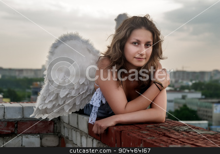 Attractive woman with angel wings on roof stock photo, Young beautiful woman with angel wings on building roof looking over city by Aikon