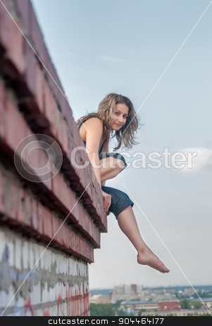 Pretty girl on roof stock photo, Young woman sitting on residental building roof by Aikon