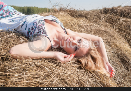 Young blond woman on hay stock photo, Young attractive blonde woman relaxing on hay stack by Aikon