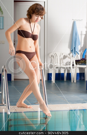 Pretty girl entering in pool stock photo, Young woman entering in pool of fitness center by Aikon