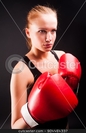 Pretty girl with boxing gloves stock photo, Young attractive woman with boxing gloves at black background by Aikon
