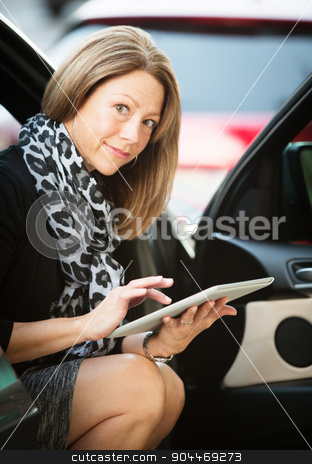 Woman Working On Tablet in Car stock photo, Business woman sitting in her car using a tablet computer by Scott Griessel