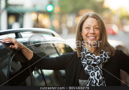 Beautiful Urban Woman Next to Car stock photo, Beautiful adult business woman outdoors standing next to car by Scott Griessel