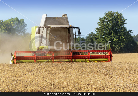 combine harvester on a golden wheat field stock photo, Dassow, Germany, August 13, 2015: combine harvester on a golden wheat field by Maren Winter