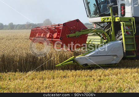 part of a combine harvester working on a wheat field stock photo, Dassow, Germany, August 13, 2015: part of a combine harvester working on a wheat field by Maren Winter