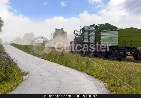 tractor with two trailers and combine harvester harvesting next  stock photo, tractor with two trailers and combine harvester harvesting next to a road in a wheat field by Maren Winter