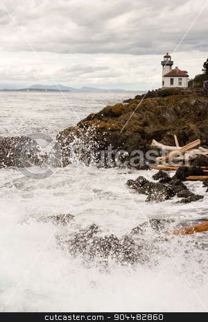 Waves Crash onto Sharp Rocks Jetty San Juan Island Lighthouse stock photo, Canada can be seen across the straight from San Juan Island by Christopher Boswell