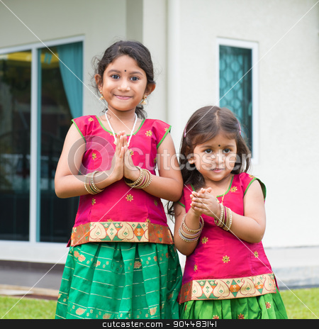 Cute Indian girls in sari greeting stock photo, Cute Indian girls dressed in sari with folded hands representing traditional Indian greeting, standing outside their new house celebrating diwali, festival of lights. by szefei