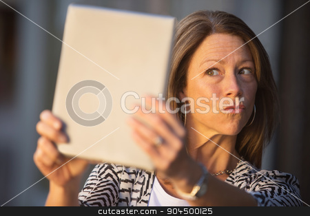 Woman Puckering Lips at Tablet stock photo, Conceited European female puckering lips at tablet computer by Scott Griessel