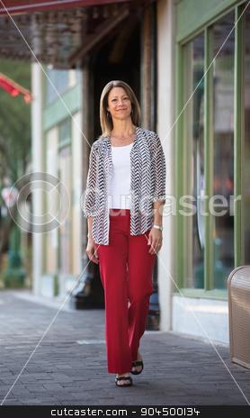 Cute Woman Walking By Theater stock photo, Cute single Caucasian woman walking outdoors near a theater by Scott Griessel