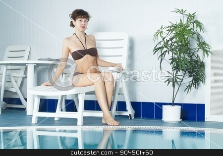Girl near pool stock photo, Young woman on deck chair near indoor pool by Aikon