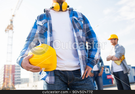 close up of builder holding hardhat at building stock photo, building, protective gear and people concept - close up of builder holding yellow hardhat or helmet at construction site by Syda Productions