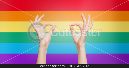 hands showing ok sign over rainbow background stock photo, people, gay pride, gesture and homosexual concept - human hands showing ok sign over rainbow flag stripes background by Syda Productions