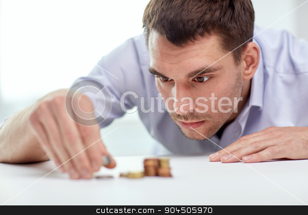 businessman with coins at office stock photo, business, people, finances and money saving concept - businessman putting coins into piles at office by Syda Productions