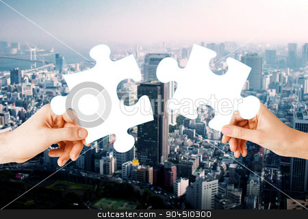 hands with green puzzle over city background stock photo, nature, ecology, energy saving, urbanization and people concept - close up of couple hands trying to connect puzzle pieces over city background by Syda Productions