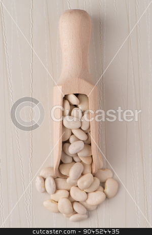 Wooden scoop with white beans stock photo, Top view of wooden scoop with white beans against white vinyl background. by Homydesign