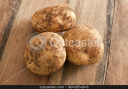 Three Unwashed Potatoes on a Wooden Table stock photo, Close up Three Unwashed Fresh Potatoes on Top of a Wooden Table. by Stephen Gibson