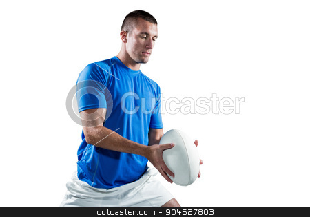 Rugby player in blue jersey holding ball stock photo, Rugby player in blue jersey holding ball against white background by Wavebreak Media