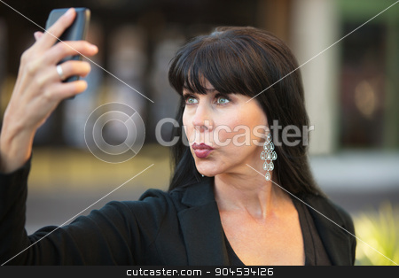 Attractive Woman Taking Selfie stock photo, Attractive woman taking selfie with black cell phone by Scott Griessel