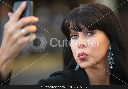 Vain Woman Taking a Self-Portrait stock photo, Attractive woman taking silly selfie with black cell phone by Scott Griessel