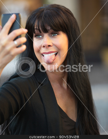 Woman Sticking Out Her Tongue stock photo, Attractive woman sticks out her tongue taking a selfie by Scott Griessel