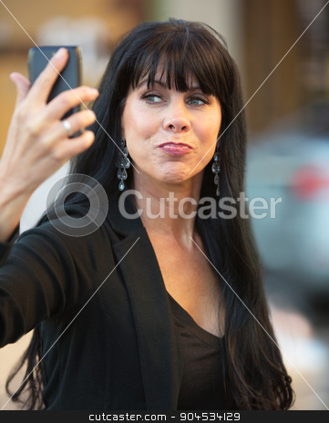Cute Woman Self-Portrait stock photo, Attractive woman taking selfie with black cell phone by Scott Griessel