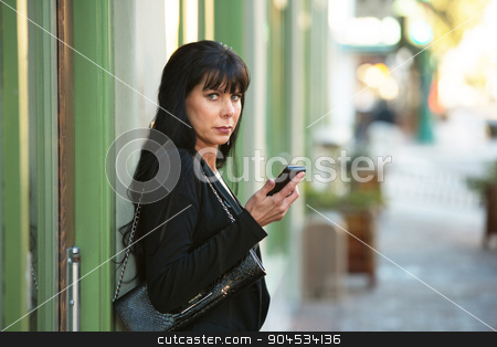 Beautiful Woman with her Cellphone stock photo, A beautiful woman holding cellphone on a downtown street by Scott Griessel