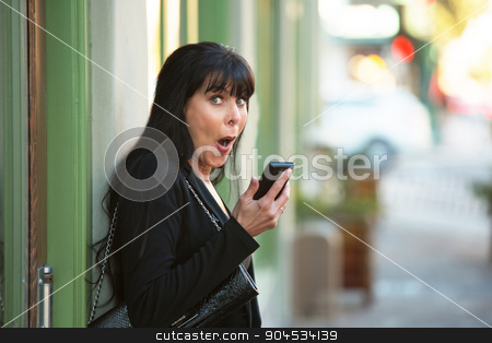 Laughing Woman with Phone stock photo, Attractive woman with cellphone on downtown street by Scott Griessel