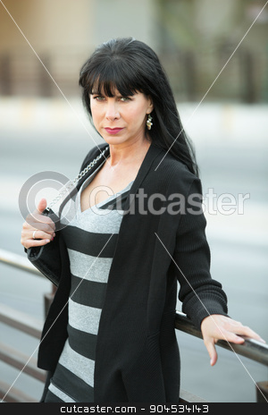 Woman Leaning Against Railing stock photo, Attractive woman on downtown street leans against a railing by Scott Griessel