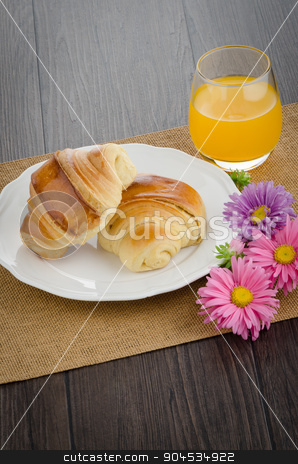 Croissants with orange juice stock photo, Closeup of croissants with orange juice with flowers on wooden table by Homydesign